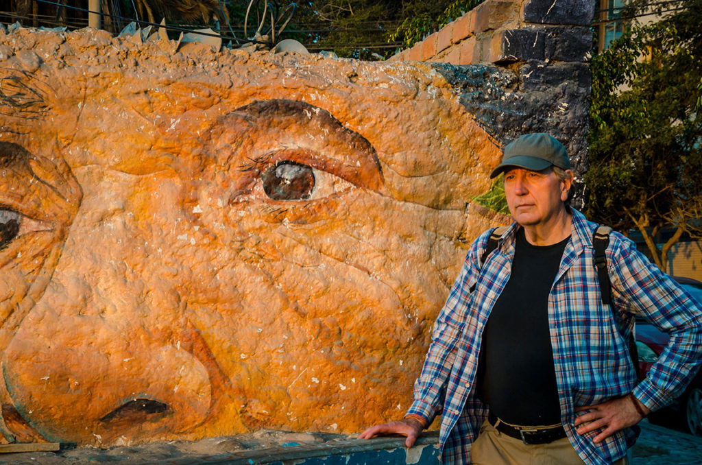 Ed in front of a mural of a man's face - Peru