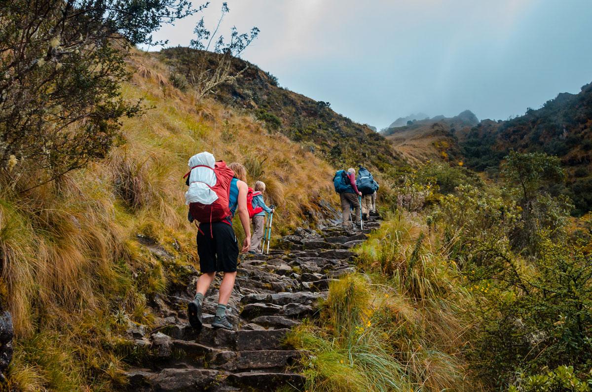 Hikers climbing steps to Runcuracay Pass - Inca Trail