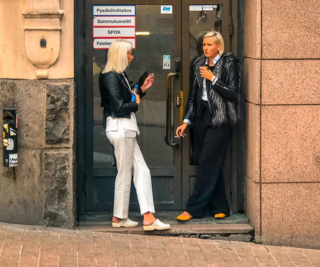 Two women smoking outside a building - Helsinki