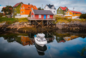 Boat in front of a red house on stilts - Henningsvaer