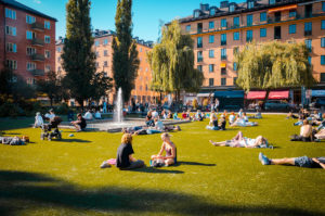 People relaxing around a fountain in Nytorget Park, Sweden