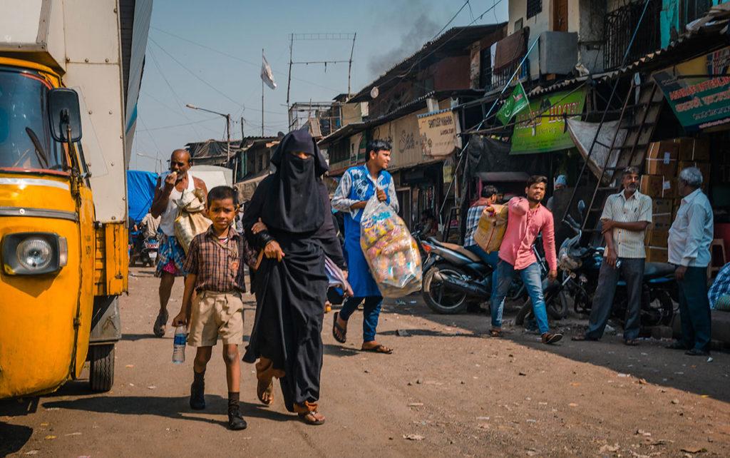 People walking on a dirt road - Dharavi