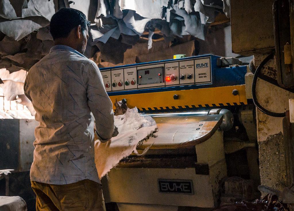 Man operating a leather-making machine - Dharavi