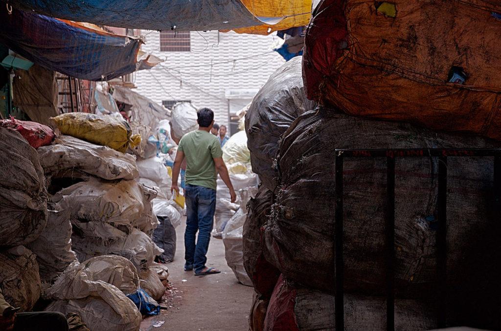 Men between stacks of recyclable junk items - Dharavi