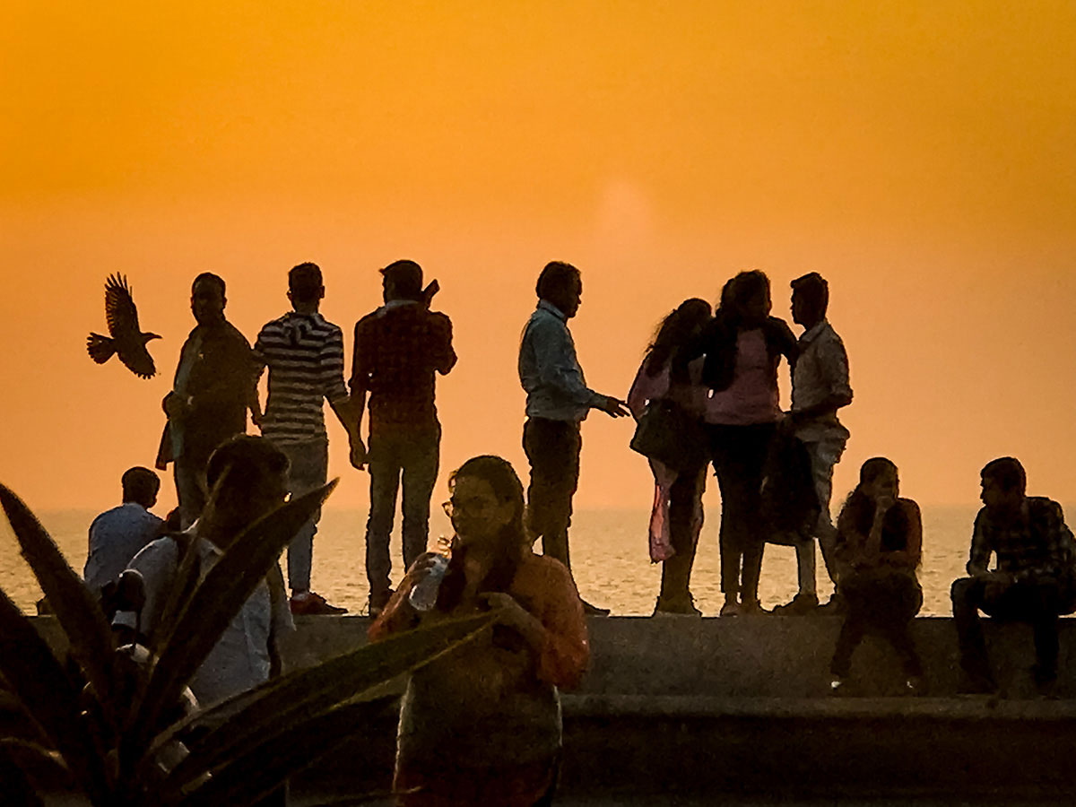 Group of young people in front of a sunset view - India