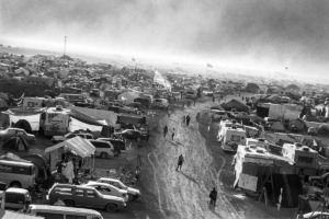 Burning Man attendees walking the desert road surrounded by parked cars and tents